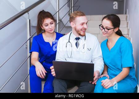 La asistencia sanitaria. Un grupo de estudiantes Los estudiantes de medicina se comunica en frente de un ordenador portátil. Discusión del diagnóstico.