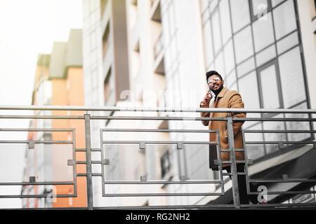 Joven empresario indio hablando por teléfono en la ciudad, en frente del edificio moderno.