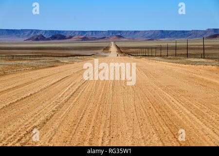 Infinitas largo camino a través de la estepa graminosa con montañas - Namibia África