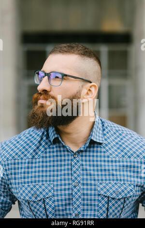 Retrato del empresario hipster barbudo con gafas y camiseta plaid