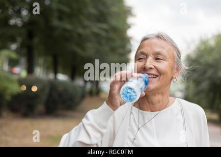 Feliz mujer senior en el exterior de la botella de agua potable