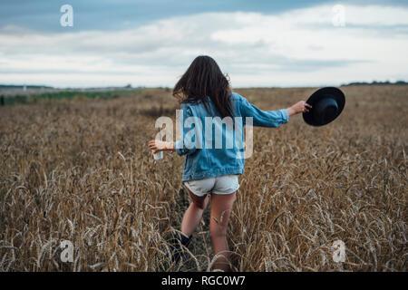 Vista posterior de la mujer joven con bebidas y hat caminar en el campo de maíz