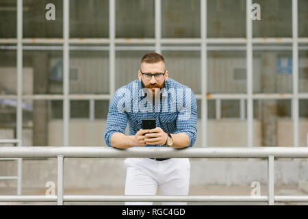 Retrato de quebrantahuesos hipster empresario con smartphone recostada en la baranda