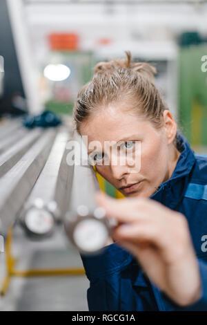 Joven que trabaja como un trabajador calificado en una empresa de alta tecnología, comprobando las varillas de acero