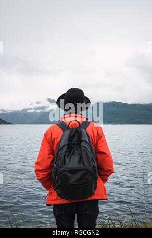 Joven parado por el agua, mirando a la distancia, vista trasera