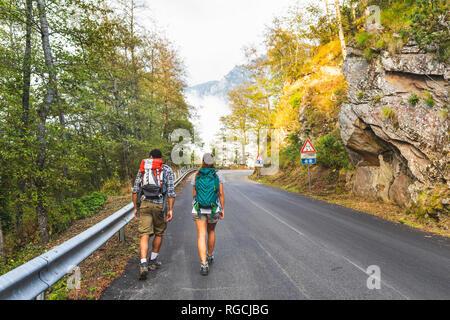 Italia, Massa, vista trasera de la joven pareja caminando sobre el asfalto de los Alpes Apuanos montañas