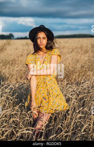 Retrato de joven mujer vistiendo ropa de verano con diseño floral y un sombrero bailando en el campo de maíz