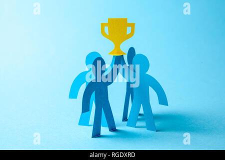 Negocio exitoso equipo ganador de la copa de oro tiene en sus manos. Team building. Líder y trabajadores alcanzan la meta
