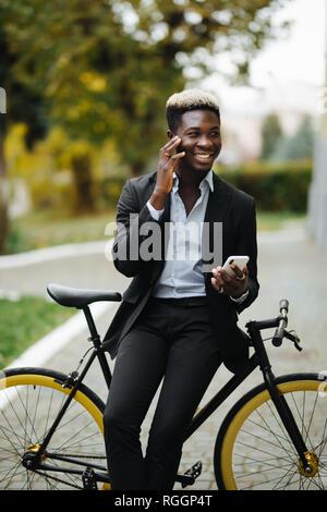 Apuesto joven hombre vestido con traje africano habla por teléfono mientras camina con bicicleta al trabajo por la mañana. El empresario va a trabajar con su bicicleta.