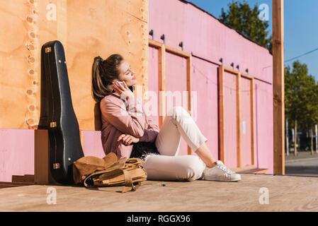 Sonriente joven mujer sentada en la plataforma junto a la guitarra caso escuchando música