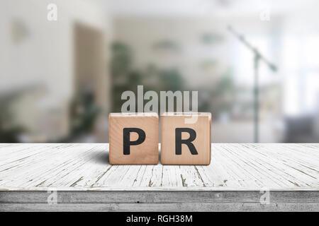 PR firmar sobre una mesa desgastada en una sala luminosa, con plantas verdes y un micrófono.