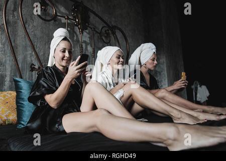 Tres mujeres con toallas alrededor de su cabeza en la cama usando celulares