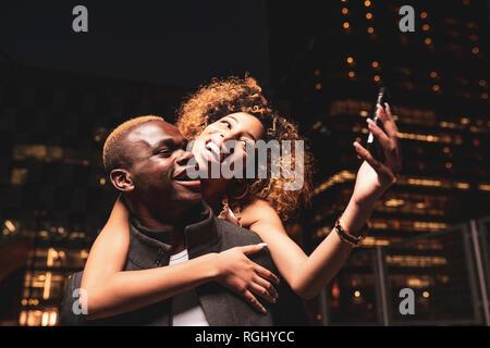 Feliz pareja joven teniendo selfie durante la noche en la ciudad