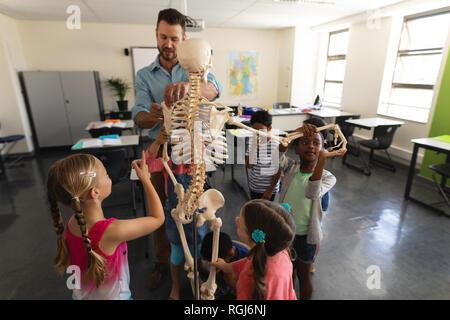 Profesor explicando el esqueleto modelo masculino en el aula de la escuela primaria