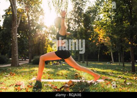 Colocar joven practicando yoga en un parque