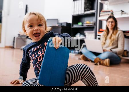 Feliz niña sentada en el suelo en casa con tablet y madre en segundo plano.