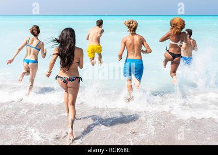 Grupo de Amigos divirtiéndose en la playa, corriendo en el agua