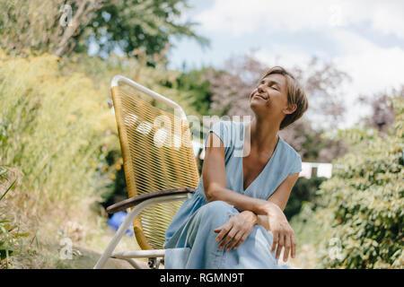 Relajado mujer sentada en el jardín en una silla con los ojos cerrados