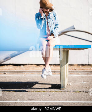 Relajado joven sentado en la mesa de tenis de mesa escuchando música Foto de stock