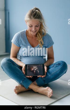 Sonriente mujer embarazada sentada en el suelo mostrando imágenes de ultrasonido en tablet pc