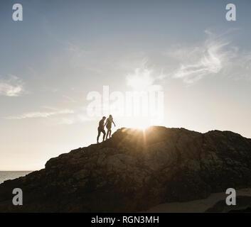 Francia, Bretaña, joven pareja de escalada en roca en la playa en el atardecer.