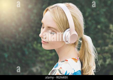 Joven mujer blanca tiene sus ojos cerrados y se mueve por escuchar música en sus auriculares
