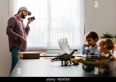 Padre grabando un archivo de audio, mientras los niños están utilizando su ordenador portátil