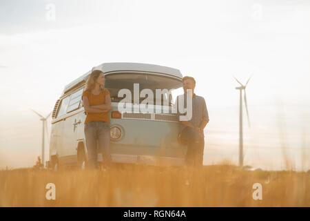 Feliz pareja en autocaravana en paisaje rural con turbinas de viento en segundo plano.