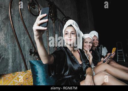 Tres mujeres con toallas alrededor de su cabeza en la cama tomando un selfie