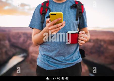 Joven holding red cup y utilizando el smartphone Foto de stock