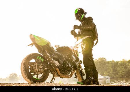 Biker hombre y la motocicleta con el río de fondo, Rider moto viaje en la calle, a la orilla del río, disfrutando de la libertad y un estilo de vida activo.