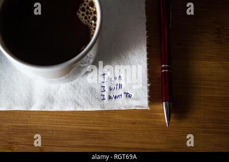 Nota manuscrita en una servilleta manchada de café con un mensaje de empoderamiento, puedo yo quiero.