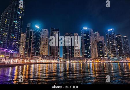 Dubai, Emiratos Árabes Unidos - Diciembre 26, 2017: el paisaje urbano de Dubai Marina District de noche. Edificios con luces del reflejo en el agua. Arquitectura o estructura y diseño. Viajes y vacaciones.