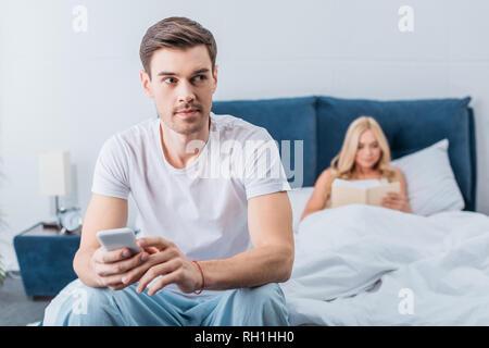 Joven Hombre sujetando el smartphone y apartar la mirada mientras novia libro de lectura en la cama detrás