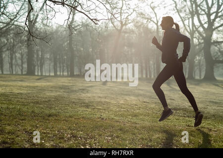 Mujer en invierno temprano por la mañana se ejecute en el mantenimiento del parque Monte escuchando música a través de auriculares.