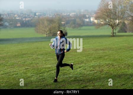 Mujer en invierno a primera hora de la mañana recorren Park mantenerse en forma haciendo ejercicio