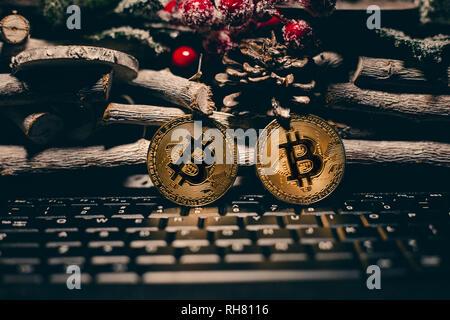 Encendido permanente Bitcoin en el teclado con la navidad de fondo. Dos oro brillante bitcoins en tiempo chrstimas sobre fondo de madera.