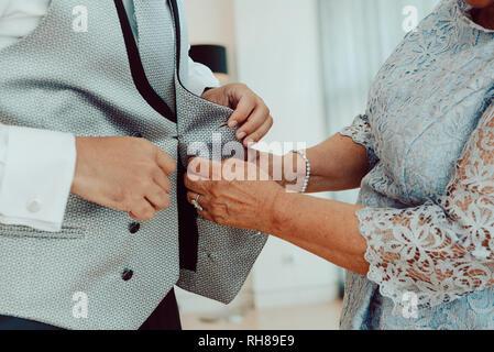 Vista lateral de la mujer cosecha ayudando a botón arriba chaleco de macho en la camisa blanca