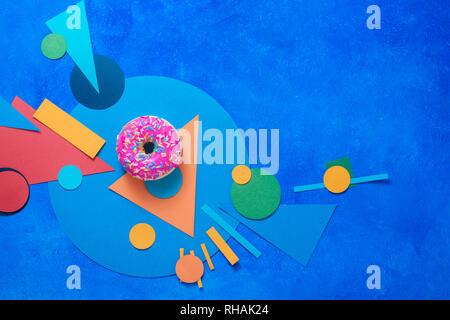 Donut glaseado rosa sobre un fondo de colores con formas geométricas. El bloque de color plano de alimentos se acostó con espacio de copia.