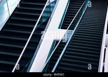 Un patrón repetido de líneas lineales es parte de una característica arquitectónica de una escalera moderna en un espacio público. Foto de stock