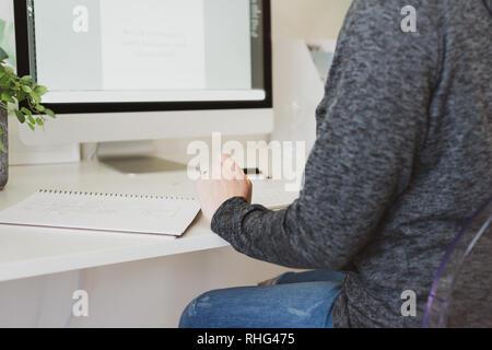 La mujer en el hogar, oficina, detrás de la vista de una mujer anónima en una mesa de trabajo