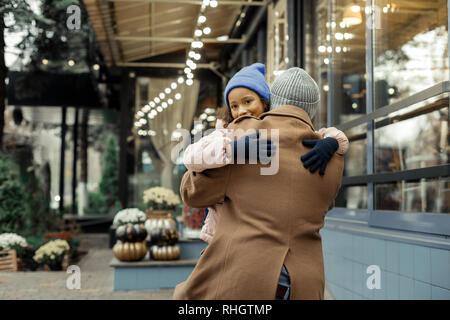 Cute dark-eyed girl rizado vistiendo sombrero azul abrazando a su padre