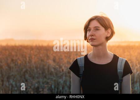 Contraluz retrato de una mujer en el atardecer. Persona de sexo femenino, de pie en la noche la luz del sol en un campo