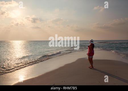 Maldivas vacaciones turismo - una mujer viendo la puesta de sol sobre el Océano Índico desde la playa, concepto - viajes; Rasdhoo ATOLL, Maldivas Asia