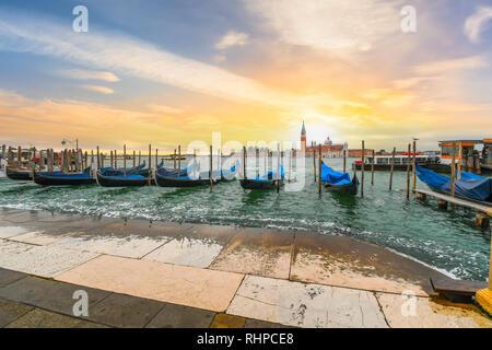 Sol detrás de la Iglesia de San Giorgio Maggiore y su Campanario a lo largo de las góndolas aparcadas en la Plaza de San Marcos, el Gran Canal de Venecia Italia