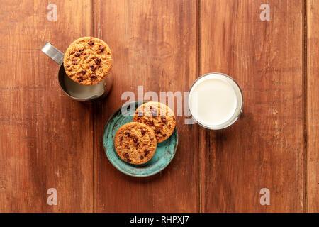 Una fotografía aérea de galletas de chocolate oscuro sobre un fondo de madera rústica con leche y copie el espacio