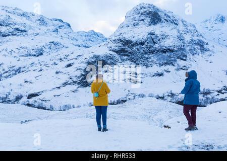 Turistas mirando las montañas cubiertas de nieve de las Tres Hermanas, desde el punto de vista off A82 en Glencoe, Highlands, Escocia en invierno Foto de stock