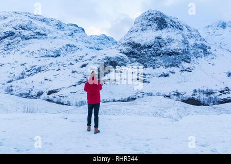 Turista mirando las montañas cubiertas de nieve de las Tres Hermanas, desde el punto de vista off A82 en Glencoe, Highlands, Escocia en invierno Foto de stock