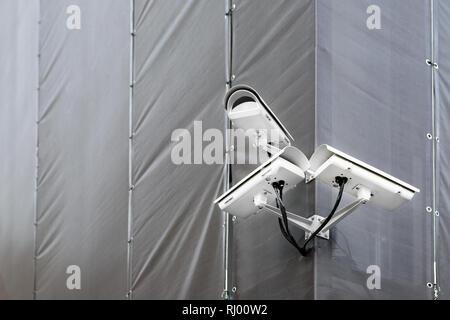 Tres cámaras CCTV en la esquina del edificio en restauración o renovación exterior. Cámaras de seguridad en el muro de la construcción en las calles de la ciudad