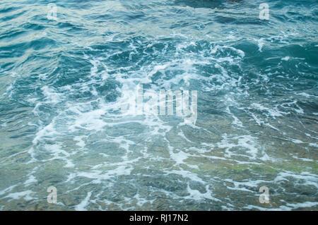 Fondo azul abstracto de la superficie del mar espumoso.